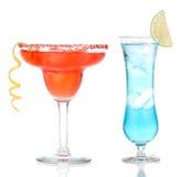 在变冷的盐的红色和蓝色玛格丽塔酒鸡尾酒为玻璃装边 免版税库存照片