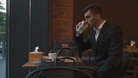在变冷静的无尾礼服饮用的柠檬水的年轻英俊的商人在一个热的夏日 现代咖啡馆背景 股票录像