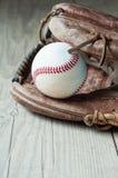 在变老的老和破旧的使用的皮革棒球体育手套 免版税库存图片