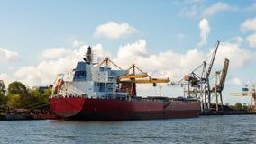 在口岸停泊的大红色bulker货船在货物操作时 库存照片