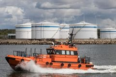 在口岸油港的背景的一条快速的小船 库存照片
