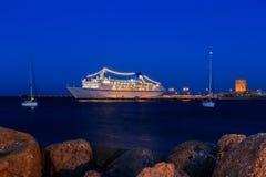 在口岸的游轮在两条航行的游艇黄昏之间 免版税库存照片