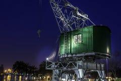 在口岸的老起重机在夜之前 免版税库存图片