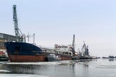 在口岸的货船在码头附近在冰中的冬天 图库摄影