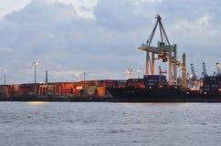 在口岸的集装箱船在日落 免版税库存照片