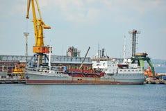 在口岸起重机下的泵浦挖泥机船 免版税图库摄影