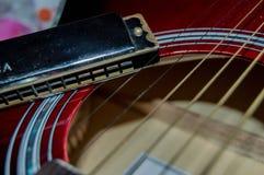 在口琴旁边的一些吉他串 免版税库存照片