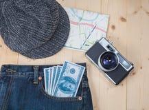 在口袋斜纹布、帽子和地图的金钱 图库摄影