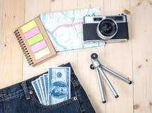 在口袋斜纹布、帽子和地图的金钱 库存照片
