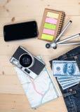 在口袋斜纹布、照相机和地图的金钱 免版税库存照片