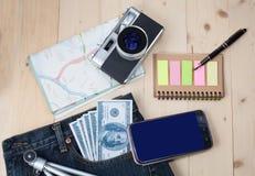 在口袋斜纹布、照相机和地图的金钱 免版税库存图片