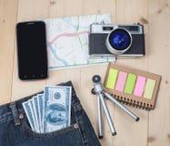 在口袋斜纹布的金钱和地图 库存照片