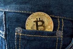 在口袋的金黄bitcoin硬币 库存照片