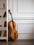 在古典内部的大提琴与书架 免版税库存照片