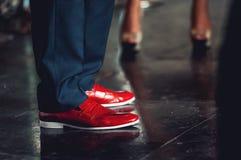 在古典裤子和时髦红色鞋子的人脚 免版税图库摄影