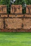 在古城墙壁前面的草地 库存图片