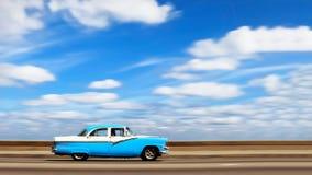 在古巴哈瓦那的首都的沿海岸区的美国明亮的蓝色减速火箭的汽车反对天空蔚蓝的与白色云彩 背景迷离弄脏了抓住飞碟跳的行动 免版税库存照片