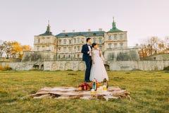 在古板的宫殿的庭院里计时消费 在期间,愉快的新婚佳偶有浪漫野餐 库存照片