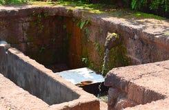 从在古老印度寺庙的水小河母牛嘴Gomukh, Karhateshwar希瓦寺庙出来 库存图片