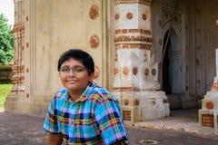 在古老印度赤土陶器寺庙o前面的年轻孟加拉男孩 免版税库存图片