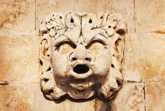 在古老喷泉的雕刻的石面具形象在圣徒一边布勒斯(StVlaha)杜布罗夫尼克,克罗地亚教会  免版税库存图片