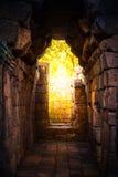 在古老岩石的城堡的隧道金黄光 免版税库存图片