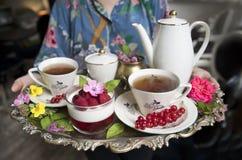 在古老杯子的壮观的新鲜的热的茶在一个银色葡萄酒盘子和莓点心,一个古色古香的茶壶 免版税库存照片