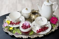 在古老杯子的壮观的新鲜的热的茶在一个银色葡萄酒盘子和莓点心,一个古色古香的茶壶 库存图片
