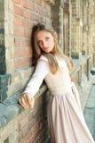 在古老砖墙附近的热情的蓝眼睛的女孩 免版税库存图片