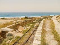 在古老罗马废墟中的老意大利铁轨在利比亚的地中海海岸大莱普提斯的 免版税库存照片