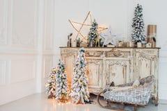 在古老葡萄酒老洗脸台五斗橱的圣诞节装饰 手工制造工艺礼物、candels和一棵树在 免版税图库摄影