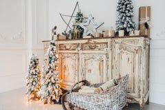 在古老葡萄酒老洗脸台五斗橱的圣诞节装饰 手工制造工艺礼物、candels和一棵树在 免版税库存照片