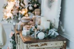 在古老葡萄酒老洗脸台五斗橱的圣诞节装饰 手工制造工艺礼物、candels和一棵树在背景 Sel 免版税库存照片