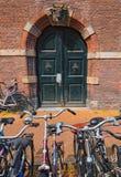 在古老门对面的葡萄酒五颜六色的自行车在老砖墙 库存图片