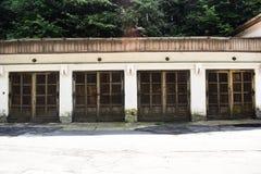 在古老难看的东西大厦的四个老车库门在被放弃的城市 库存照片