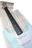 在古老音乐纸张的一把电吉他 免版税库存照片