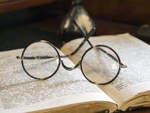 在古色古香的书的老玻璃 免版税库存照片