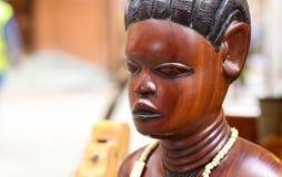 在古色古香的市场上的非洲木妇女雕塑 库存照片