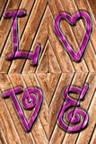 在古色古香的木头和紫色被铭记的词爱的浪漫背景以上 库存图片