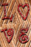 在古色古香的木头和红色被铭记的词爱的浪漫背景以上 免版税库存图片