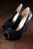 在古色古香的木背景的女性黑鞋子 免版税库存图片