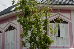 在古色古香的桃红色大厦的减速火箭的白色木窗口在减速火箭的镇 免版税库存照片