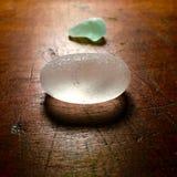 在古色古香的桌上的海滩玻璃 免版税库存照片