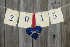 在古色古香的纸的年2015年与垂悬在晒衣绳的红色和蓝色心脏由破旧的木篱芭 免版税图库摄影