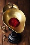在古色古香的葡萄酒铁标度碗的番红花香料在木桌上 库存图片