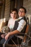 在古色古香的长凳的新婚佳偶夫妇 免版税库存图片