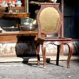 在古董店前面的老被破坏的椅子 免版税图库摄影