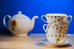 在另一边的杯一和茶壶在蓝色背景 库存图片
