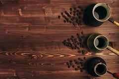 在另外亲切的破旧的土耳其罐cezve的热的咖啡与在棕色老木板背景,顶视图的拷贝空间 库存照片