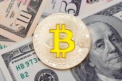 在另外美元背景的金黄黄色bitcoin 免版税库存照片